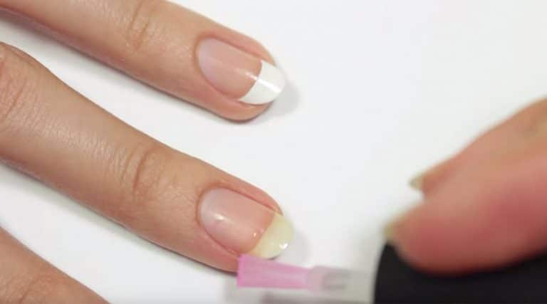 Mãos fazendo unhas francesinha
