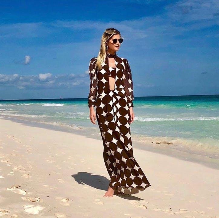 mulher na praia com óculos de sol