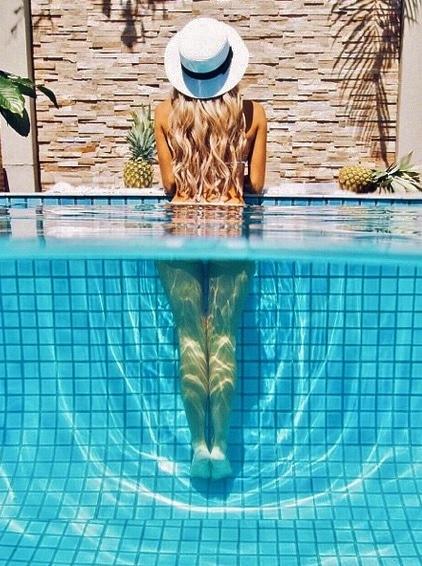 mulher com chapéu na piscina