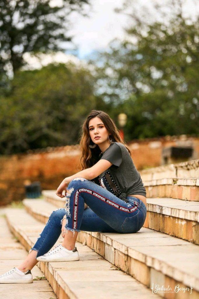 mulher de calça jeans sentada na escada