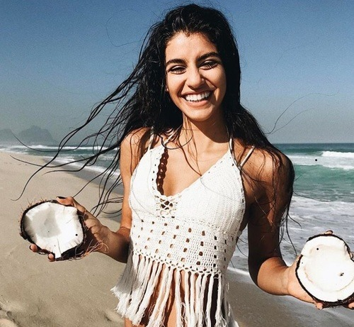 menina na praia segurando coco