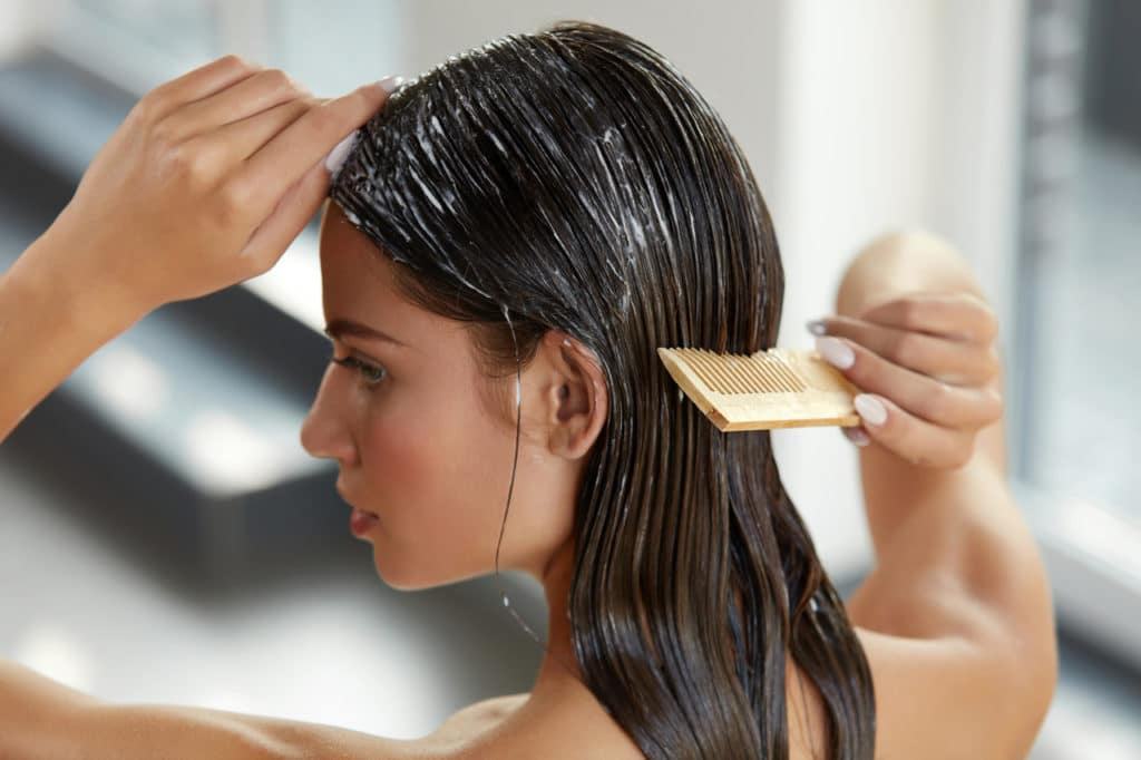 mulher com creme no cabelo