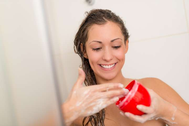 mulher passando creme no cabelo