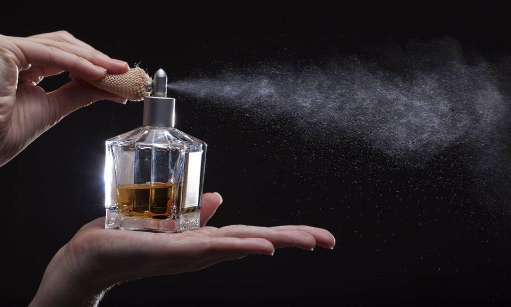 mulher espirrando perfume