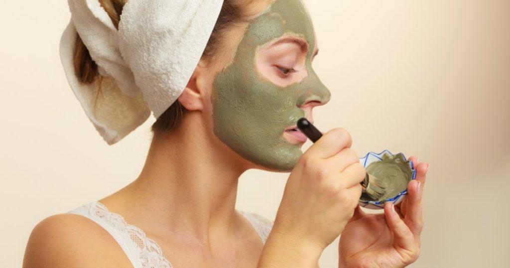 mulher passando argila no rosto
