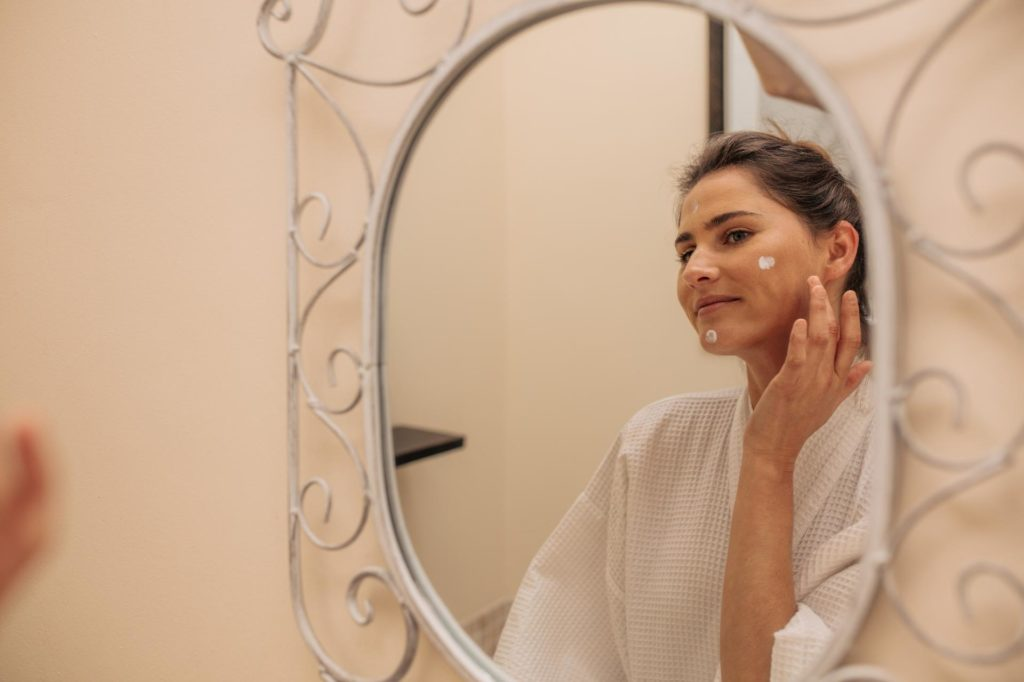 mulher passando creme no rosto
