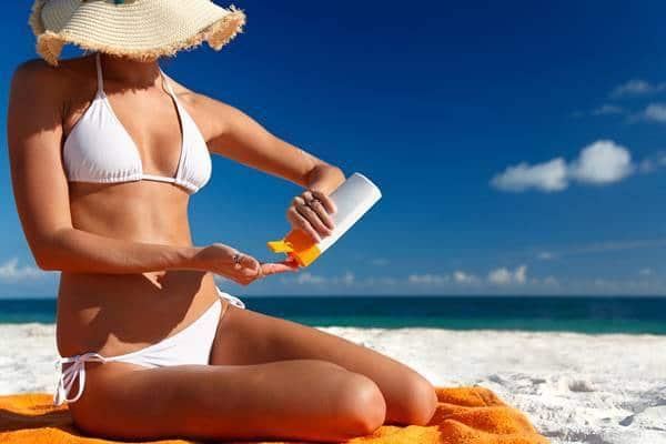 mulher na praia com protetor solar