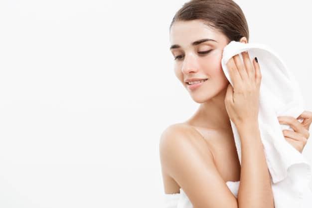 mulher limpando o rosto rotina de cuidados com a pele
